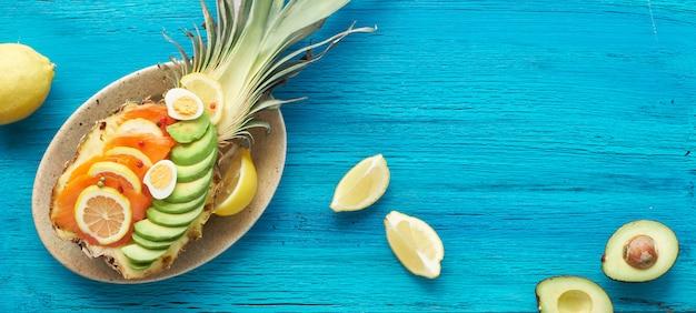 Vue De Dessus Sur Ananas Avec Saumon Fumé, Avocat, Oeufs De Citron Et De Caille, Panorama, Copy-space Photo Premium