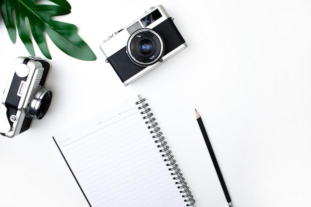 Vue de dessus de l'appareil photo argentique avec carnet, crayon et feuilles. fond blanc isolé Photo Premium