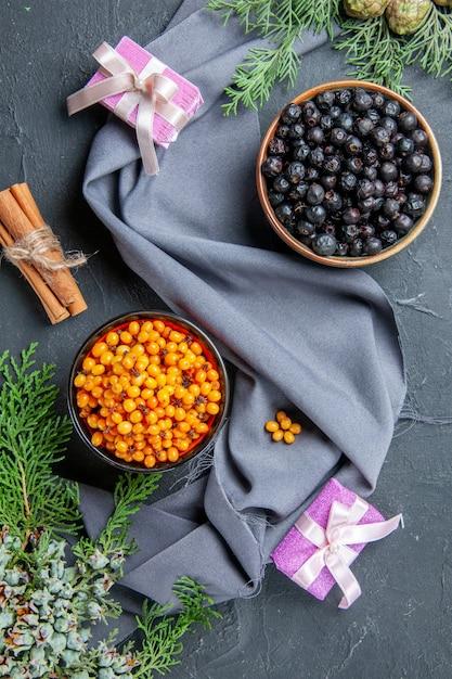 Vue De Dessus L'argousier De Cassis Dans Des Bols De Branches De Pin Châle Violet Petits Cadeaux Sur Une Surface Sombre Photo gratuit