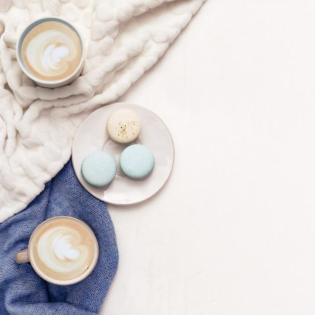 Vue De Dessus De L'art Cappuccino, Macarons Sucrés, Vêtements Chauds, Fond De Style De Vie. Café Chaud Le Matin à La Maison. Concept D'hiver. Photo Premium