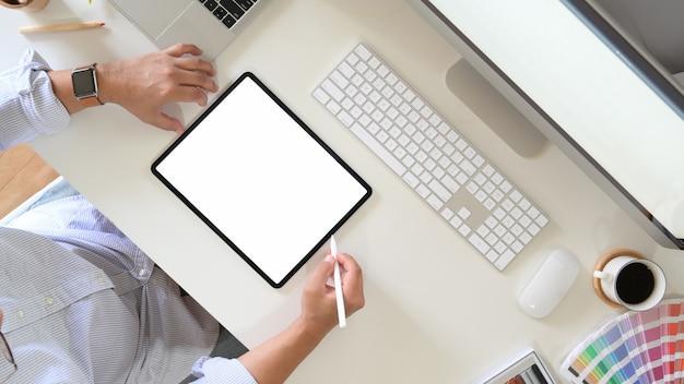 Vue de dessus d'un artiste qui dessine quelque chose sur une tablette graphique au bureau Photo Premium