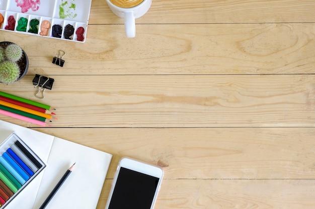 Vue de dessus artiste smartphone espace de travail, couleur, tasse de café, papier bloc-notes, cactus et crayon sur la table en bois Photo Premium
