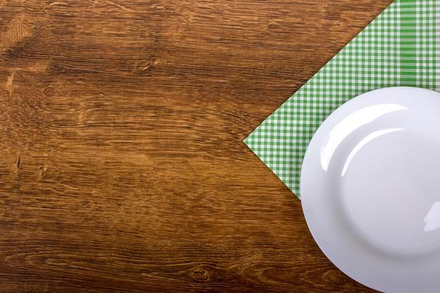 Vue de dessus d'une assiette vide propre sur fond de table en bois Photo Premium