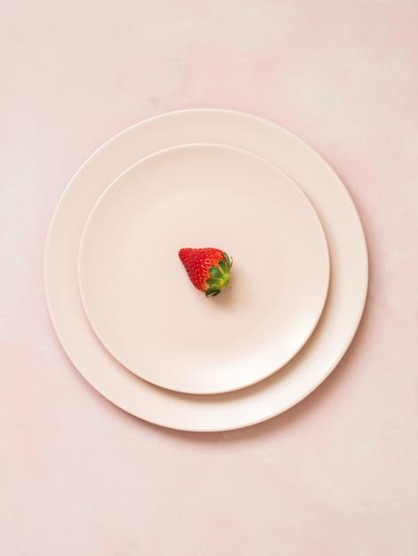 Vue de dessus des assiettes en céramique avec une fraise sur fond pastel rose Photo Premium