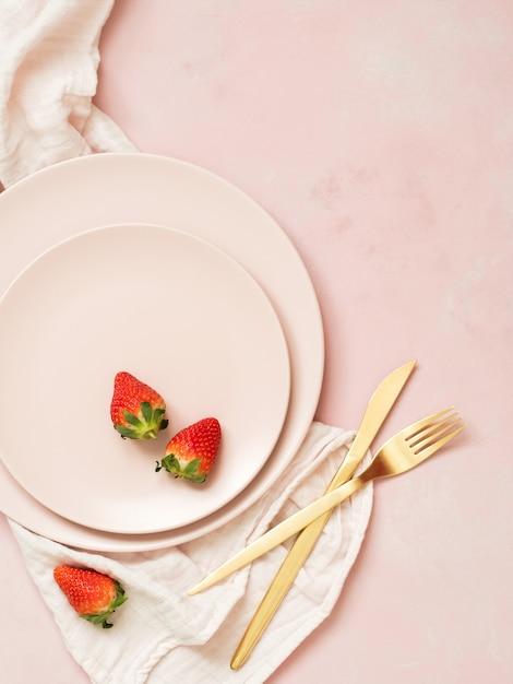 Vue de dessus des assiettes en céramique avec des fraises et des couverts dorés sur fond pastel rose Photo Premium