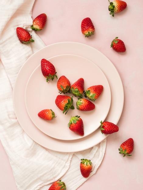 Vue de dessus des assiettes en céramique avec des fraises sur fond pastel rose Photo Premium