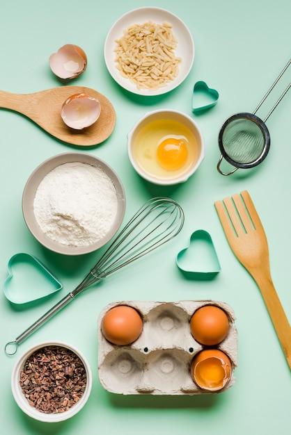 Vue De Dessus Au Fouet Avec Des œufs Et De La Farine Sur La Table Photo gratuit