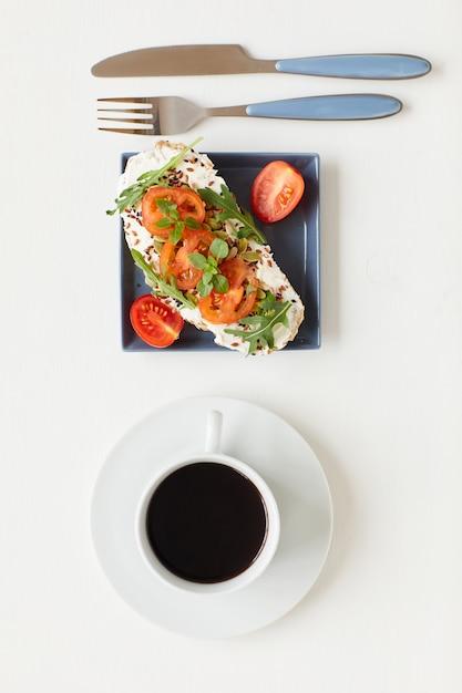 Vue De Dessus Au Petit-déjeuner Gastronomique Sain Avec Une Délicieuse Bruschetta De Remise En Forme à Côté D'une Tasse De Café Noir Sur Table Blanche Photo Premium