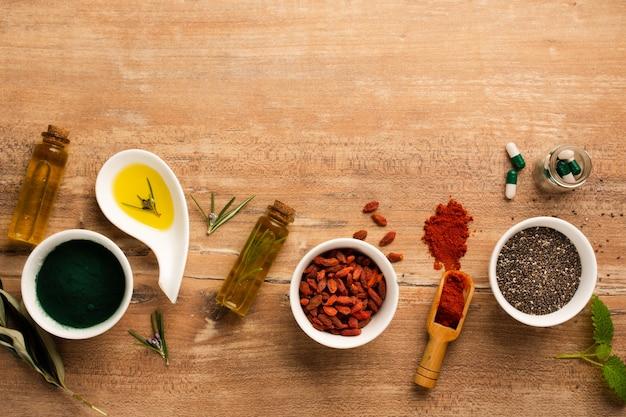 Vue De Dessus Des Baies De Goji Avec De L'huile Et Des Médicaments Sur La Table Photo gratuit
