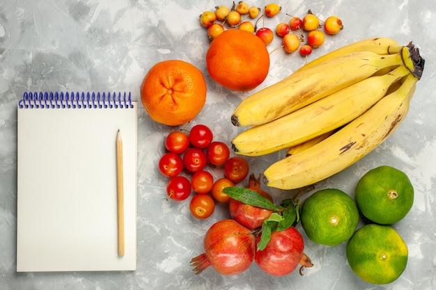 Vue De Dessus Bananes Jaunes Fraîches Avec Bloc-notes De Grenades Et Mandarines Sur Un Bureau Blanc Clair Photo gratuit