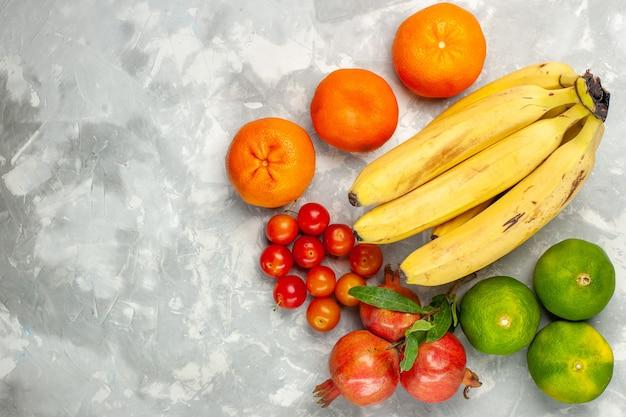 Vue De Dessus Des Bananes Jaunes Fraîches Avec Des Grenades Et Des Mandarines Sur Un Bureau Blanc Clair Photo gratuit