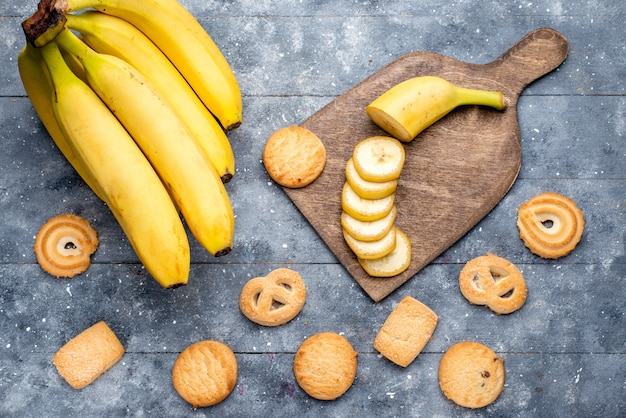 Vue De Dessus Des Bananes Jaunes Fraîches Tranchées Et Entières Avec Des Cookies Sur Des Baies De Fruits Frais Et Gris Photo gratuit