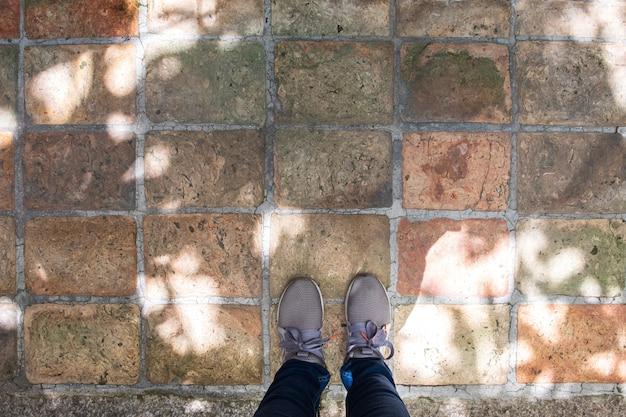 Vue de dessus des baskets grises, debout sur le sol en béton. Photo Premium