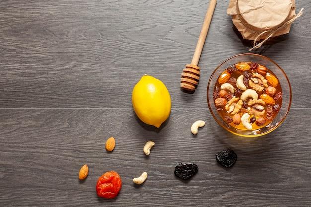 Vue de dessus bâton de miel et un bol de noix Photo gratuit