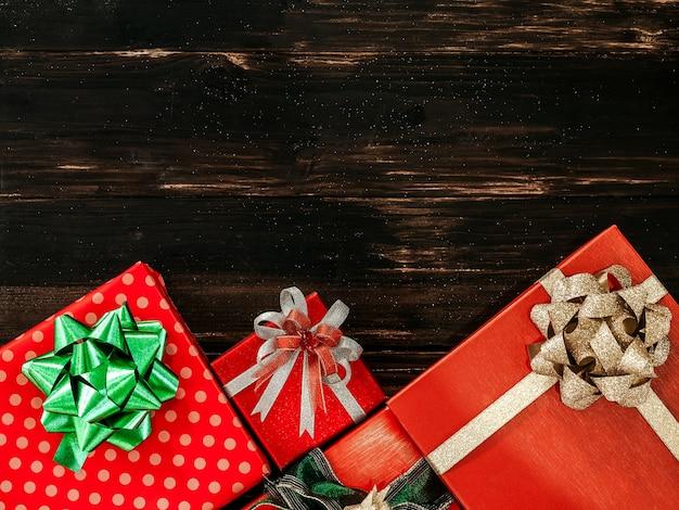 Vue De Dessus De La Belle Boîte-cadeau Rouge Avec Des Décorations D'arc Vert Et Or Brillant Sur Planche De Bois Foncé Photo Premium