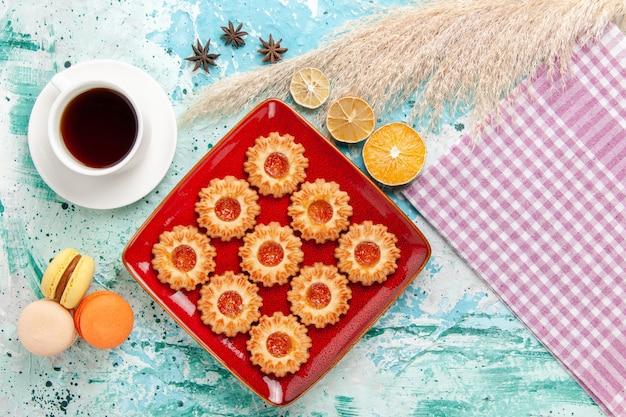 Vue De Dessus Biscuits Au Sucre Avec Tasse De Thé Et Macarons Sur Fond Bleu Photo gratuit