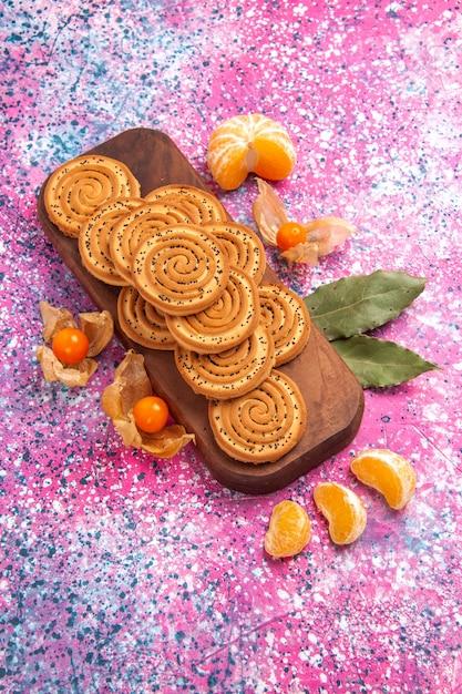 Vue De Dessus Des Biscuits Sucrés Ronds Avec Des Mandarines Sur La Surface Rose Photo gratuit