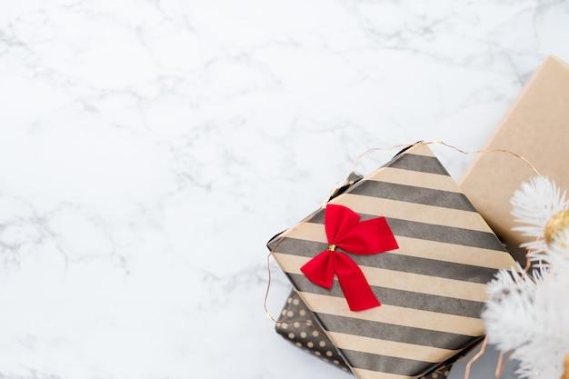 Vue de dessus de la boîte actuelle rayée moderne avec arc rouge se trouvait sous un arbre de noël blanc sur un sol en marbre blanc Photo Premium
