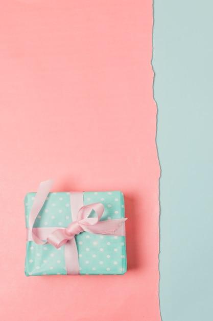 Vue de dessus de la boîte cadeau enveloppée sur une surface bicolore Photo gratuit