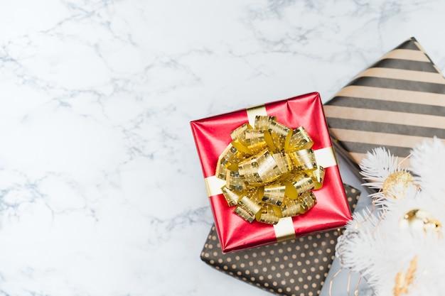 Vue de dessus de la boîte de cadeau rouge brillant avec l'arc et le ruban d'or se trouvait sous le sapin de noël blanc sur le sol en marbre blanc Photo Premium