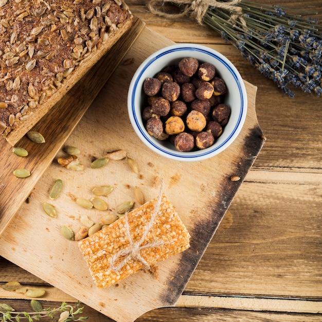 Vue de dessus d'un bol de noisettes avec pain et barre de sésame sur une planche à découper Photo gratuit