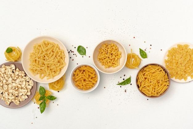 Vue de dessus des bols avec différents types de pâtes Photo gratuit