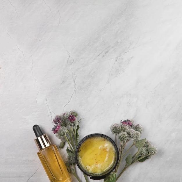 Vue de dessus de la bouteille de beurre et d'huile essentielle sur fond de marbre Photo gratuit