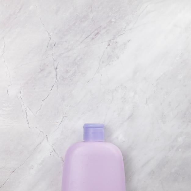 Vue de dessus d'une bouteille rose sur fond de marbre Photo gratuit