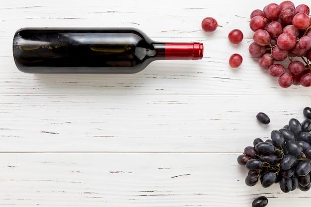 Vue de dessus bouteille de vin avec grappe de raisin Photo gratuit
