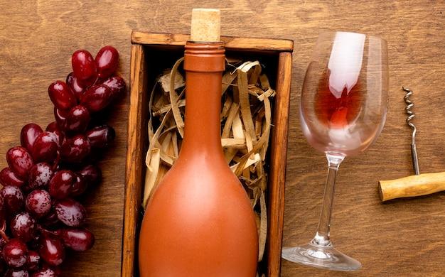 Vue De Dessus Bouteille De Vin Et Verre Avec Tire-bouchon Et Raisins Photo gratuit