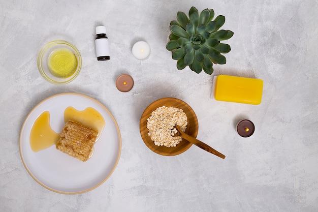 Une vue de dessus des bouteilles d'huile essentielle; l'avoine; plante de cactus; savon jaune et nid d'abeille sur fond de béton Photo gratuit