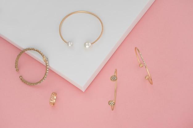 Vue De Dessus Des Bracelets Dorés Et Bague Sur Fond De Papier Rose Et Blanc Photo Premium