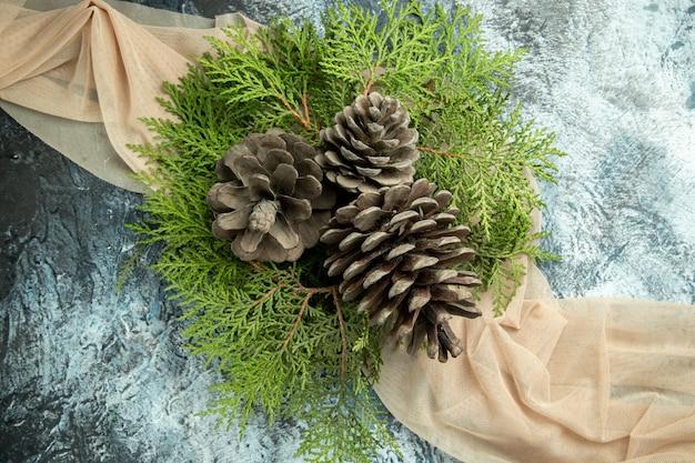 Vue De Dessus Des Branches De Pin Pinecones Sur Châle Beige Sur Surface Grise Photo gratuit