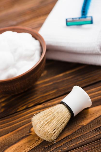 Une vue de dessus d'une brosse synthétique de rasage avec une mousse défocalisée; serviette et rasoir sur le bureau en bois Photo gratuit