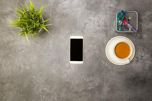 Vue de dessus de bureau avec café, plante en pot, téléphone portable et accessoires professionnels Photo Premium