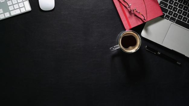 Vue de dessus de bureau en cuir foncé avec ordinateur portable et fournitures de bureau Photo Premium