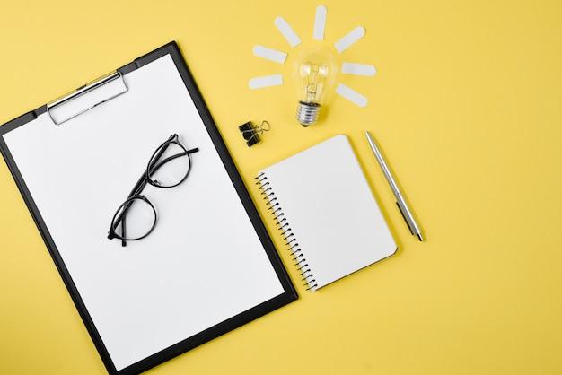 Vue de dessus de bureau espace de travail de style design fournitures de bureau avec stylo, bloc-notes, lunettes, ampoule Photo Premium