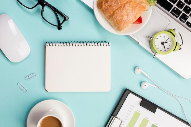 Vue de dessus d'un bureau avec papeterie, ordinateur portable, souris et réveil sur fond bleu Photo gratuit