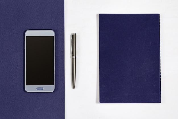 Vue de dessus sur le bureau avec smartphone, cahier, stylo. Photo Premium