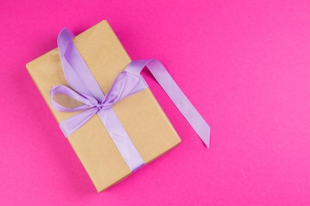 Vue de dessus d'un cadeau décoré avec un arc sur fond rose Photo Premium