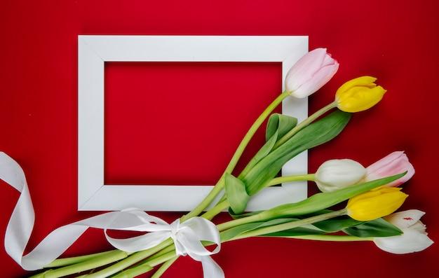Vue De Dessus D'un Cadre Photo Vide Avec Un Bouquet De Fleurs De Tulipes Colorées Sur Fond Rouge Avec Copie Espace Photo gratuit
