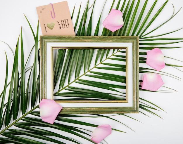 Vue De Dessus D'un Cadre Photo Vide Avec Carte Postale Sur Une Feuille De Palmier Avec Des Pétales De Fleurs Roses Sur Fond Blanc Photo gratuit