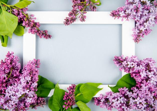 Vue De Dessus D'un Cadre Photo Vide Avec Des Fleurs Lilas Sur Fond Blanc Avec Copie Espace Photo gratuit