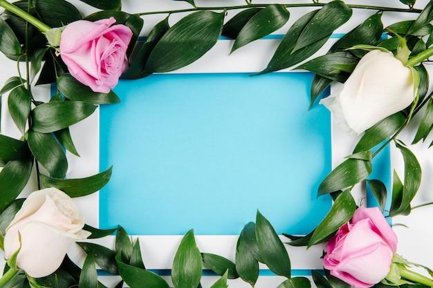 Vue De Dessus D'un Cadre Photo Vide Avec Des Roses Blanches Et Roses Et Ruscus Sur Fond Bleu Avec Copie Espace Photo gratuit