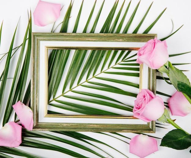 Vue De Dessus D'un Cadre Photo Vide Avec Des Roses De Couleur Rose Sur Une Feuille De Palmier Sur Fond Blanc Photo gratuit