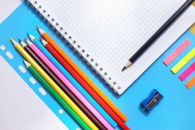 Vue de dessus sur un cahier, crayons, taille-crayon sur fond bleu. concept de retour à l'école Photo Premium