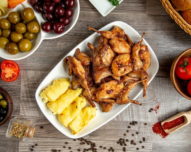 Vue De Dessus De Cailles Grillées Avec Lula Kebab De Pommes De Terre Servies Avec Des Cornichons Sur La Table Photo gratuit