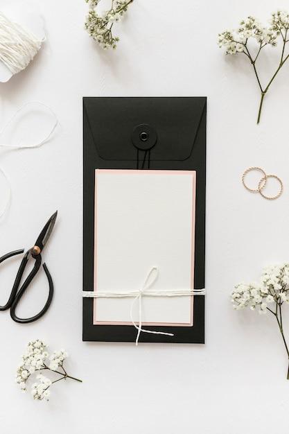 Une vue de dessus de cartes de vœux avec des ciseaux; anneaux de mariage; ficelle et fleur sur fond blanc Photo gratuit