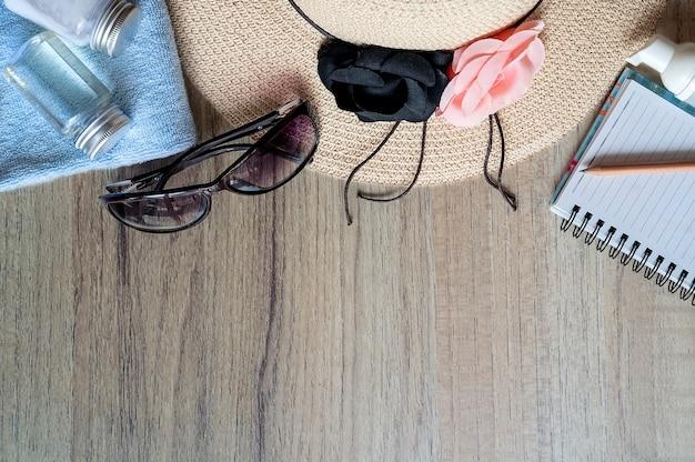 Vue de dessus, chapeau de paille, lunettes de soleil, lotion écran solaire et cahier sur la table en bois Photo Premium