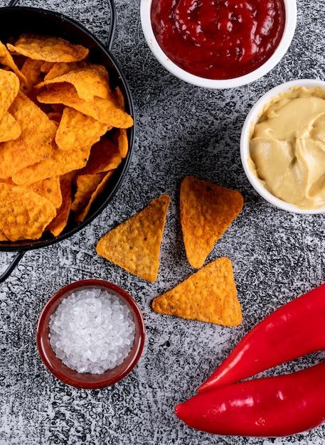 Vue De Dessus Des Chips Dans Une Poêle En Métal Noir Et Des épices Avec Des Saucisses Dans Des Bols Sur La Pierre Blanche Verticale Photo gratuit